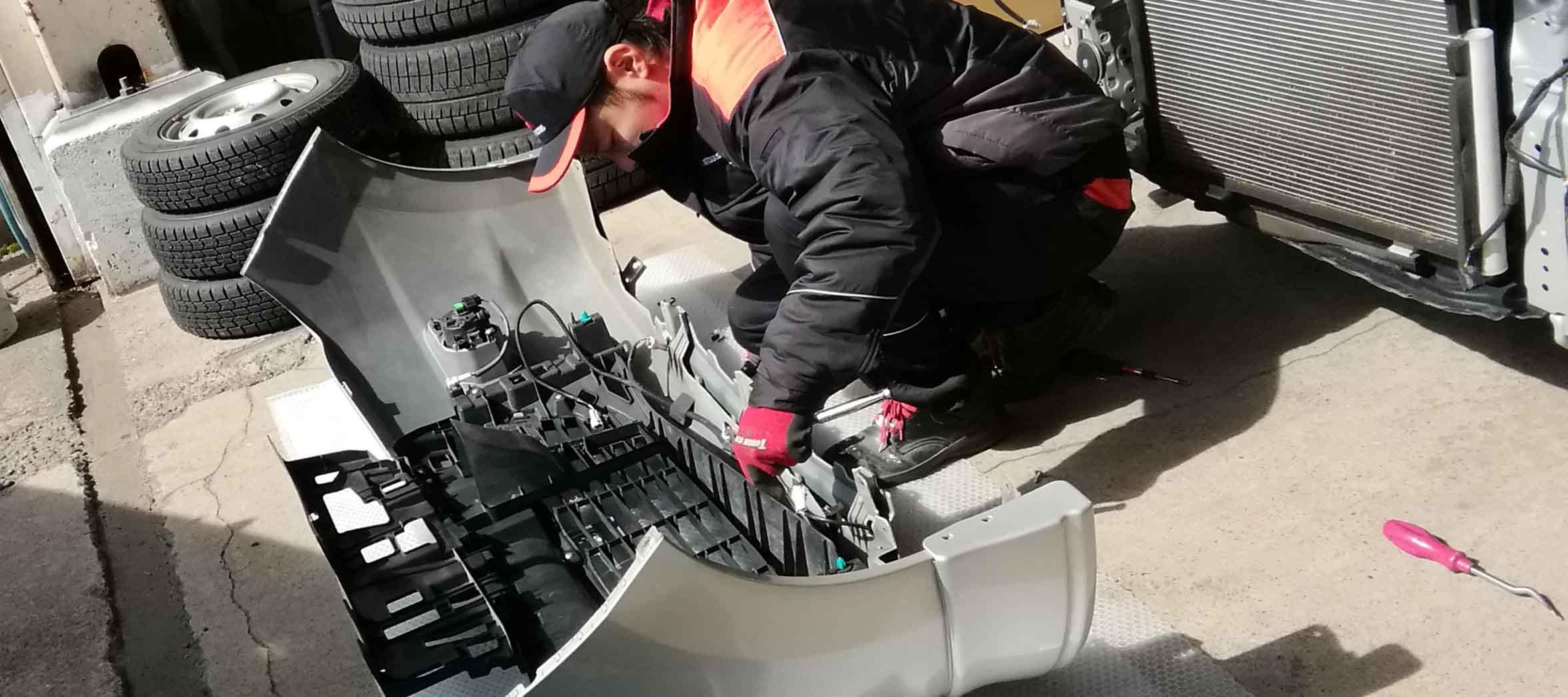 バンパーを修理する社員